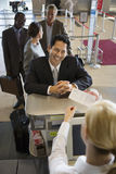 Businessman standing at airport check-in counter, smiling, female attendant looking at ticket, elevated view Royalty Free Stock Photography