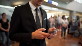 Businessman standing in airport hall, typing a message on phone, business trip stock photography