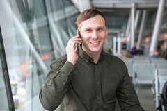 Businessman standing at the airport,talking by cellphone . stock image