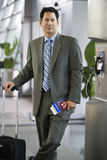 Businessman standing in airport terminal with luggage and ticket, smiling, portrait Stock Photography