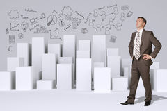 Businessman standing akimbo. Many white cubes with Royalty Free Stock Image