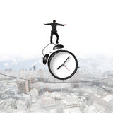 Businessman standing on alarm clock balancing tightrope Royalty Free Stock Images