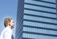 Businessman standing alone. In front of a big blue business building Royalty Free Stock Photography