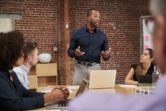 Free Businessman Standing And Leading Office Meeting Around Table Royalty Free Stock Photos - 144596538