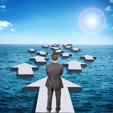 Businessman standing on arrow in sea Stock Photos