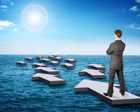 Businessman standing on arrow in sea Stock Images