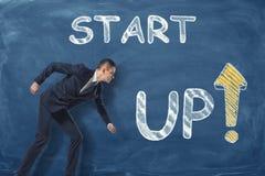 Businessman standing as if he is going to run near phrase `start up` written on dark blue wall. Stock Photos