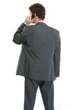 Businessman standing back and speaking mobile Stock Photography