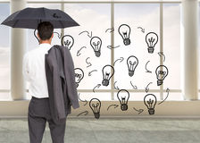 Businessman standing back to camera holding umbrella and jacket on shoulder Royalty Free Stock Photo