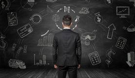 Businessman standing back to us looking at the blackboard with chalk financial drawings Stock Image