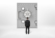 Businessman standing back to us looking at the giant safe door, all isolated on the grey background. Stock Photography