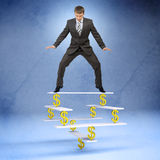 Businessman standing on balance with dollar sign Royalty Free Stock Images