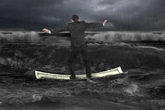 Businessman standing balancing on money boat floating in dark oc Royalty Free Stock Photography