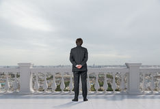 Businessman standing on balcony. And looking to city Stock Photos