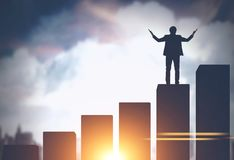 Businessman standing on bar chart in city. Silhouette of a young businessman standing on a bar chart against a big city sky background. Concept of business Royalty Free Stock Images
