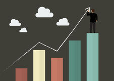 Businessman standing on bar graph drawing a growth chart Stock Photo