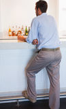 Businessman standing at the bar holding glass of whiskey. At the local bar Royalty Free Stock Image