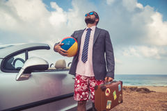 Businessman standing on a beach near car. Successful young businessman on a beach. Man standing near cabriolet classic car. Summer vacations and travel concept Stock Images