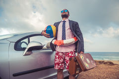 Businessman standing on a beach near car Stock Images