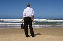 Businessman standing on beach relaxing looking at horizon, retirement planning concept. Businessman standing on a beautiful beach looking at horizon distance Stock Photography