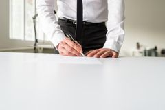 Businessman standing behind his office desk signing a document royalty free stock image