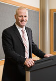 Businessman standing behind podium royalty free stock photography