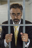 Businessman Standing Behind Prison Cell Bars Stock Image