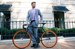Businessman standing with bicycle outdoors Stock Image