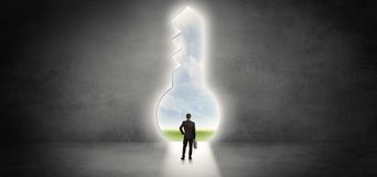 Businessman standing in a big keyhole Stock Images