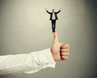 Businessman standing on big thumbs up Royalty Free Stock Images