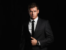 Businessman standing on black background. handsome young Man in suit Royalty Free Stock Photography