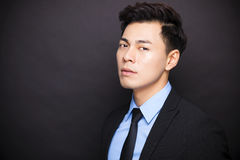 Businessman standing before black background. Young businessman standing before black background Stock Photo