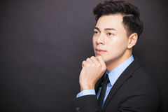 Businessman standing before black background. Young businessman standing before black background Royalty Free Stock Photo
