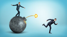 A businessman standing on a black round bomb with a lit fuse beside a man running away from it. Business competition. Drastic measures. Flee from trouble Stock Images