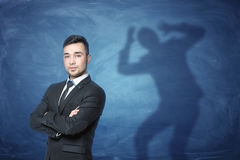 Businessman standing on blue background with a shadow with hands on head behind him Royalty Free Stock Images