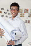 Businessman standing with blueprints in the office, portrait Royalty Free Stock Image
