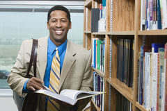 Businessman Standing By Bookshelf Stock Photos