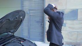 Businessman standing by broken car with open hood, talking over phone, breakdown. Stock footage stock footage