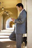 Businessman standing in building arcade, looking at text message on mobile phone, profile Royalty Free Stock Photography