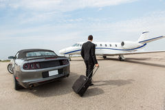 Businessman Standing By Car And Private Jet At. Businessman with luggage standing by car and private jet at airport terminal royalty free stock photography
