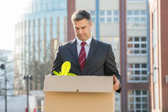 Businessman Standing With Cardboard Box Outside Office Stock Images