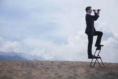 Businessman standing on a chair and looking through a telescope in the middle of the desert stock images