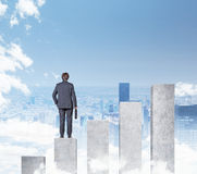 Businessman standing on chart Stock Image
