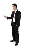 Businessman standing, checking on phone Stock Photo
