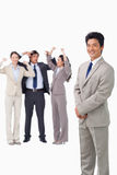 Businessman standing with cheering team behind him Stock Image