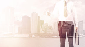 Businessman standing at cityscape background Stock Photo