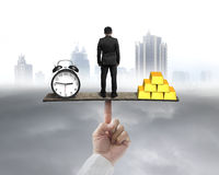 Businessman standing between clock and gold balancing on seesaw Royalty Free Stock Photo