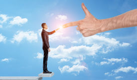 A businessman standing among the clouds to touch fingers with a giant hand. Stock Photos