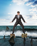 Businessman standing on coins above sharks Royalty Free Stock Image