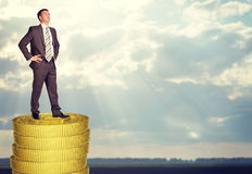 Businessman standing on coins stack Royalty Free Stock Photos
